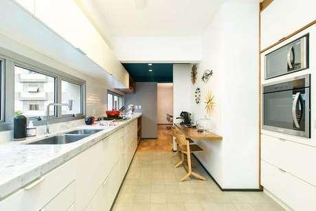 19. Cozinha compacta estilo corredor com a cor branca predominante. Projeto de DT Estúdio