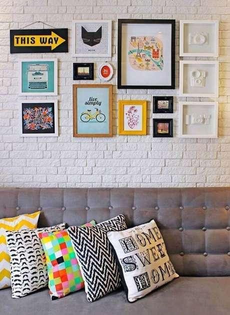12. Decoração com vários quadrinhos e almofadas coloridas para sofá cinza – Foto: Girls Universe Blog