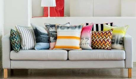 13. Sofá decorado com vários modelos diferentes de capas de almofadas coloridas – Foto: