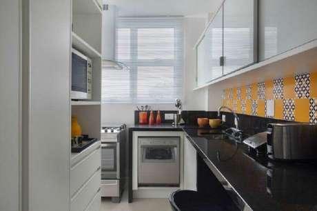 5. Decoração em tons de preto e branco, com azulejo hidráulico para cozinha compacta com armários que possuem portas de correr