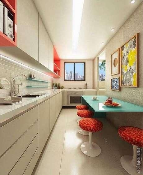 10. Decoração para cozinha pequena com mesa azul e banquetas vermelhas