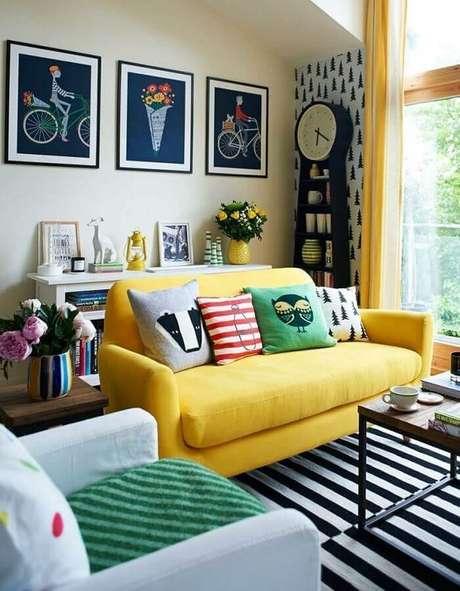 36. Decoração para sala com tapete preto e branco listrado e capas de almofadas coloridas para sofá amarelo – Foto: Dani Guedes