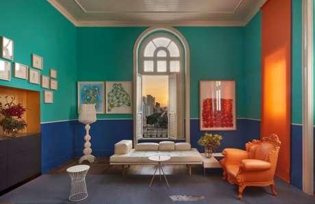 8. Decoração de sala de estar azul e turquesa com poltrona laranja e tons de verde – Por: Casa Cor