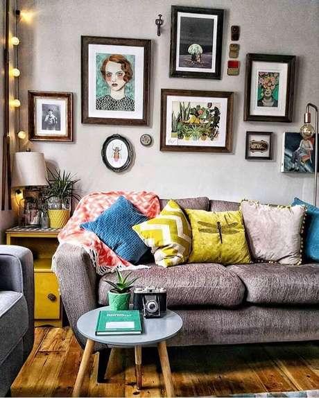 52. Sala decorada com vários quadros e almofadas coloridas para sofá cinza – Foto: DIYCores