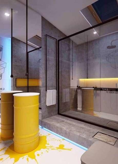 12. Banheiro moderno decorado com cimento queimado e tonel decorativo amarelo – Foto: Pinosy