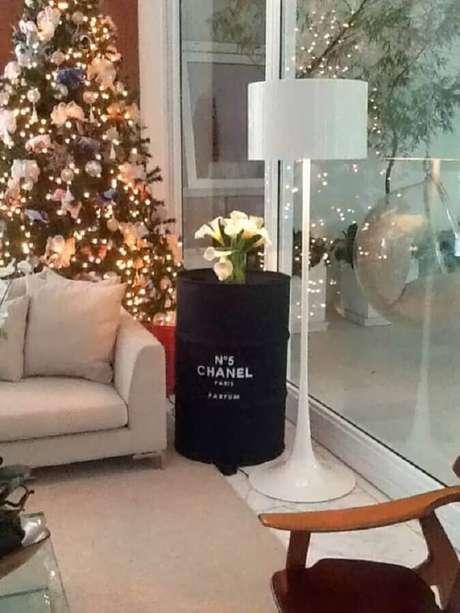 29. Sala decorada com árvore de natal e tonel decorativo preto com logo da Chanel – Foto: Casa com Moda