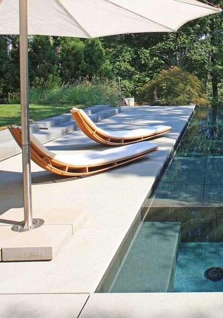 39. Decoração para área externa com piscina e espreguiçadeira de madeira com design arrojado – Foto: Pinterest