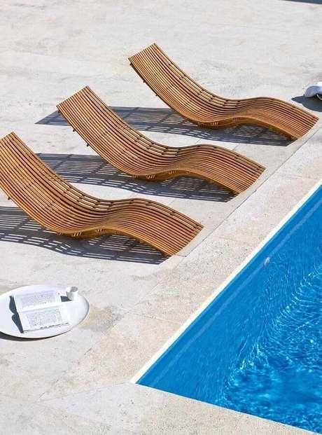 51. Decoração para área externa com piscina e cadeira espreguiçadeira de madeira com curvas modernas – Foto: Pinosy