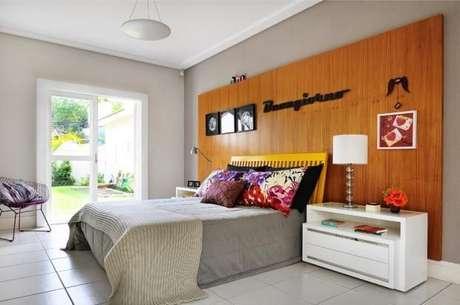 63. O painel de madeira de um quarto de casal moderno pode também ter quadros. Projeto por: Milena Aguiar