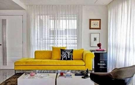 38. Sala de estar decorada com sofá amarelo e tonel decorativo preto com logo da Chanel – Foto: Ingrid Raggio