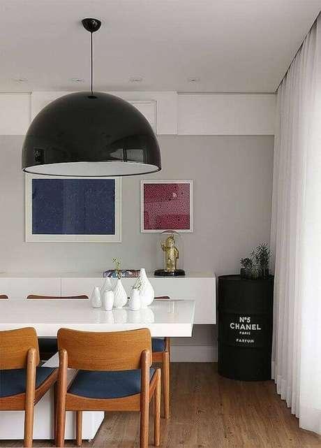 42. Sala de jantar moderna decorada com mesa branca e tonel decorativo preto com logo da Chanel – Foto: Casa 2 Arquitetos