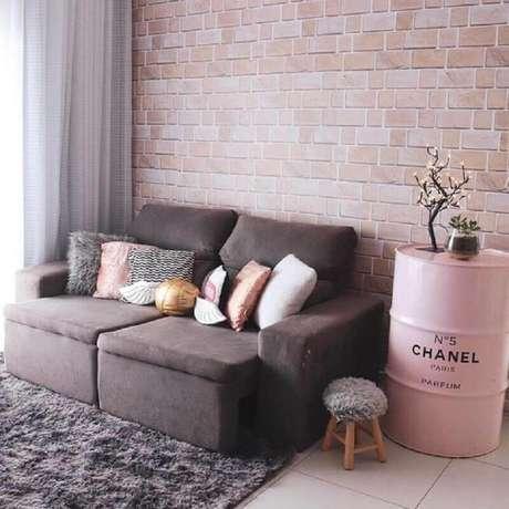 43. Sala de estar decorada com parede de tijolinho e tonel decorativo rosa com logo da Chanel – Foto: We Heart It