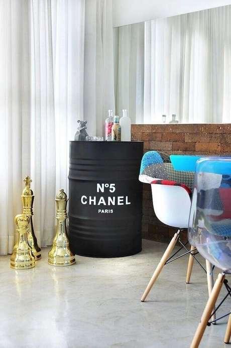 61. Sala de jantar decorada com tonel tambor decorativo preto com o logo da Chanel – Foto: IBD Arquitetura