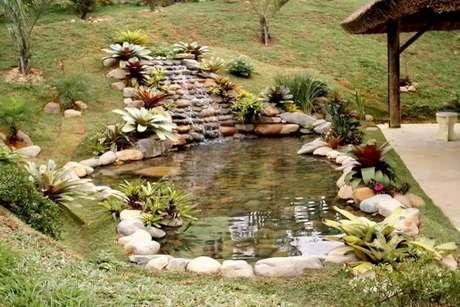 2. O lago artificial decorado com pedras e uma pequena cascata adornada de flores foi feito para encantar a área externa casa sem atrapalhar a passagem – Por: Ideia de casa