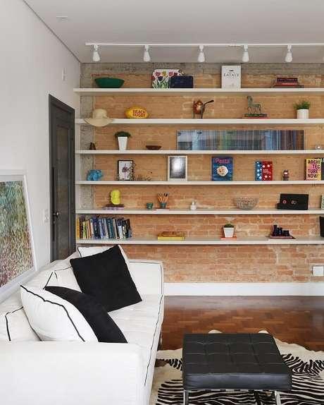 73. Parede de tijolinho e prateleiras com madeira branca encantam a decoração. Fonte: Tua Casa