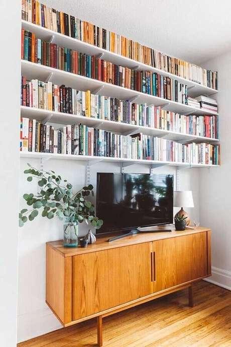 77. Prateleira para livros acima do rack da sala de estar. Fonte: Pinterest