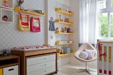 62. Prateleira para livros na cor amarela e nichos brancos complementam a decoração do quarto de bebê. Fonte: Pinterest