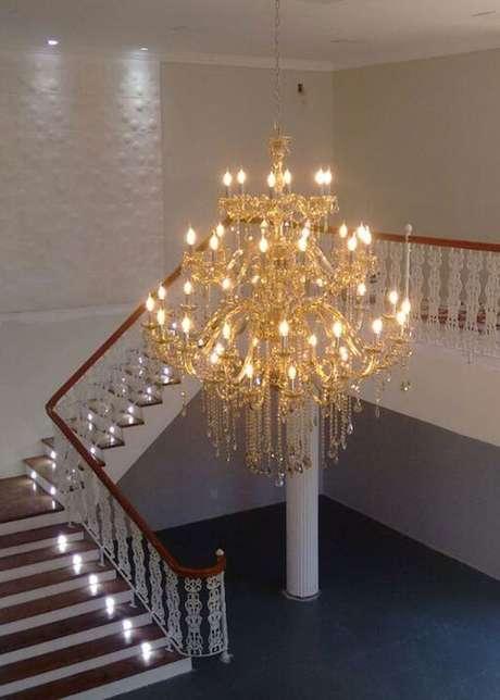 17. Ambientes altos podem contar com o lustre candelabro dourado para compor a decoração – Por: New Light