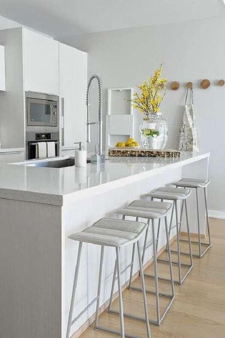 15. Decoração para cozinha branca com ilha e ganchos redondos de madeira – Foto: Sweet Harmonie