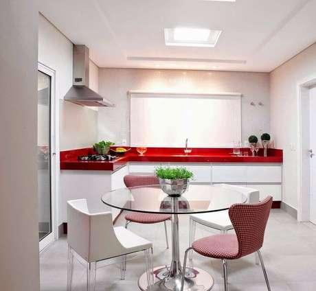 17. Decoração para cozinha branca com bancada vermelha e mesa redonda de vidro – Foto: Diego Araujo Rodrigues