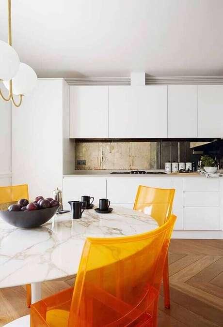 7. Decoração para cozinha branca com cadeiras de acrílico laranja dando um toque de personalidade ao ambiente – Foto House and Garden
