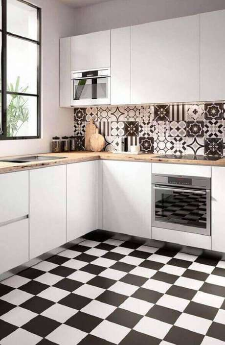 47. Decoração para cozinha branca com piso xadrez preto e branco e azulejo estampado – Foto: Pinosy