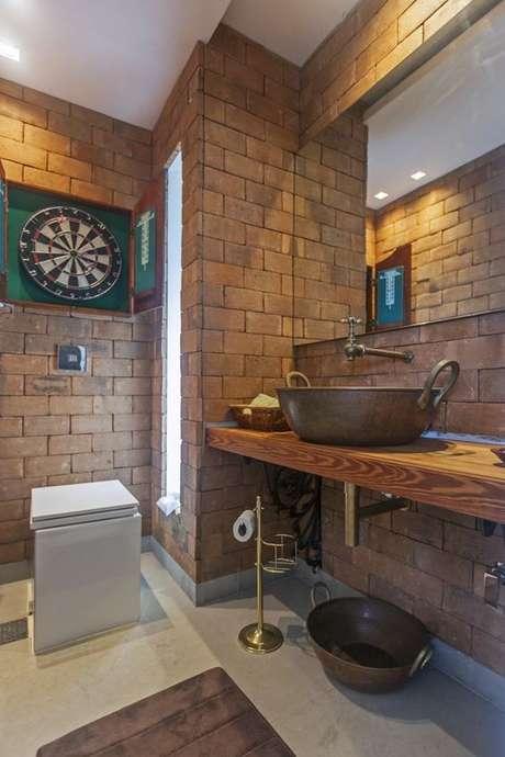 5. A bancada de madeira dá um tom rústico ao banheiro. Foto: Haus Decoração