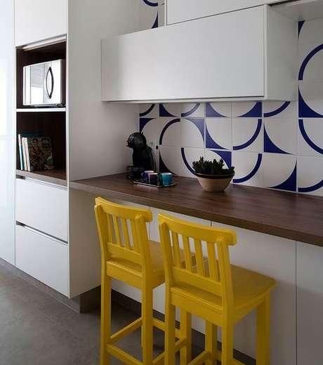 20. A bancada de madeira associada a armários também otimiza espaço. Foto: Casa de Valentina