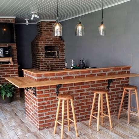 62. Áreas externas ficam ótimas com uma bancada de madeira. Foto: Tua Casa