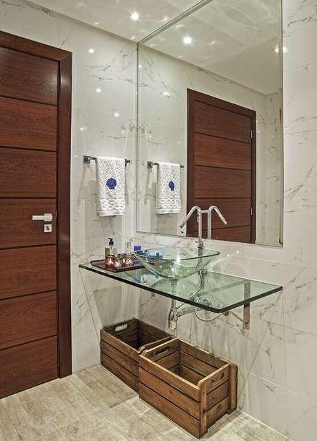 8. Banheiro com cuba de vidro e caixas de madeira para guardar itens de banheiro com facilidade