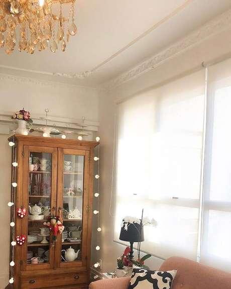 33. Decoração para sala com lustre e cristaleira de madeira com louças antigas – Foto: Marta Mousquer