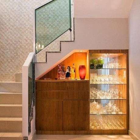 36. Decoração com barzinho de madeira e cristaleira moderna embaixo da escada – Foto: Carla Lima Interiores