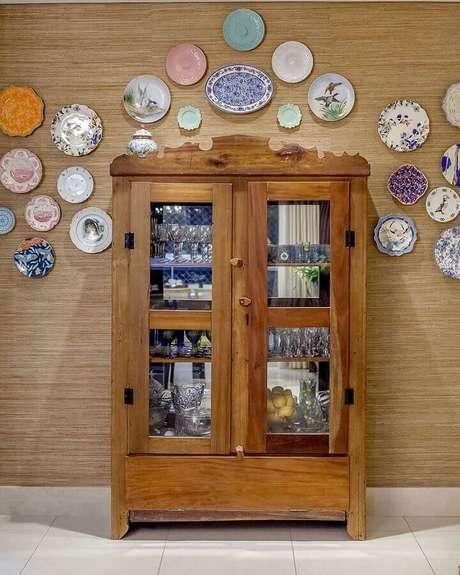37. Ambientes decorado com cristaleira de madeira e vários pratos decorativos na parede – Foto: Carla Lima Interiores