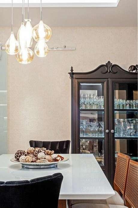 66. Sala de jantar decorada com luminária moderna e cristaleira antiga – Foto: Patricia Azoni