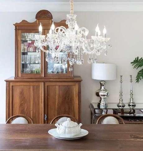 69. Sala de jantar decorada com lustre de cristal e cristaleira antiga de madeira – Foto: Stefani Arquitetura