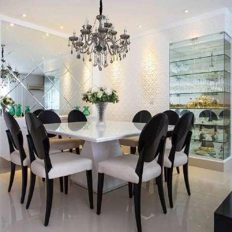 72. Sala de jantar sofisticada decorada com lustre candelabro e cristaleira de vidro – Foto: Viviane Maistro Giampini