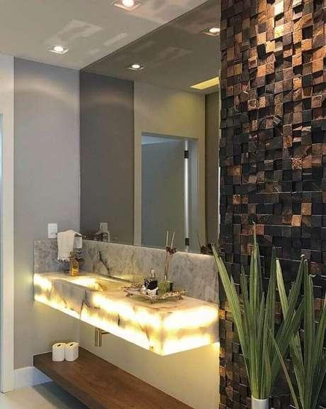 12. Decoração para banheiro com bancada com iluminação embutida e pedra ferro – Foto: Ximene Villar