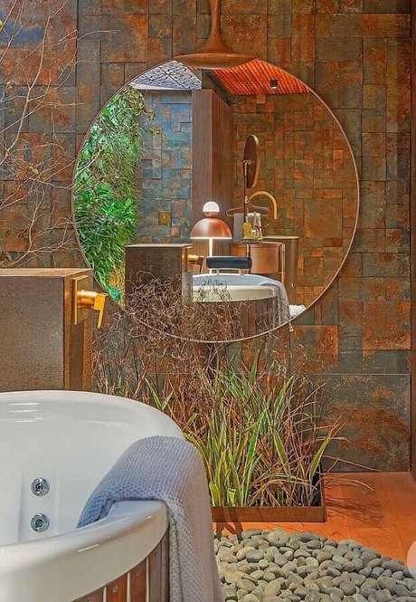 21. Decoração para banheiro com banheira, espelho redondo e revestimento pedra ferro – Foto: Mister Cryl Tintas
