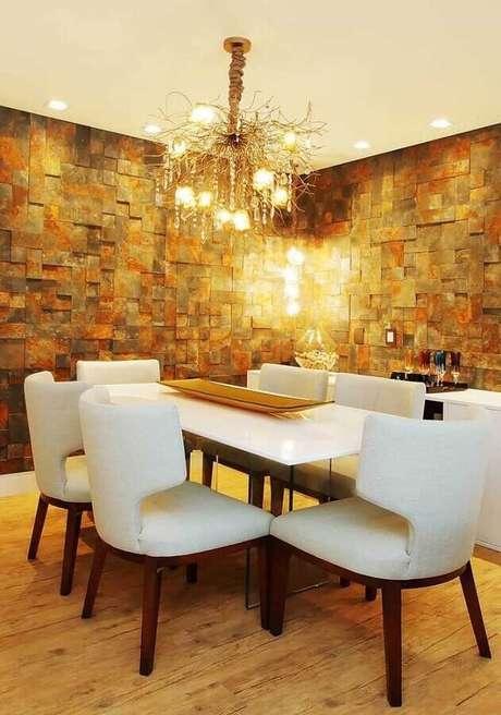22. Decoração para sala de jantar com cadeiras brancas, lustre arrojado e parede com revestimento pedra ferro – Foto: Pinterest