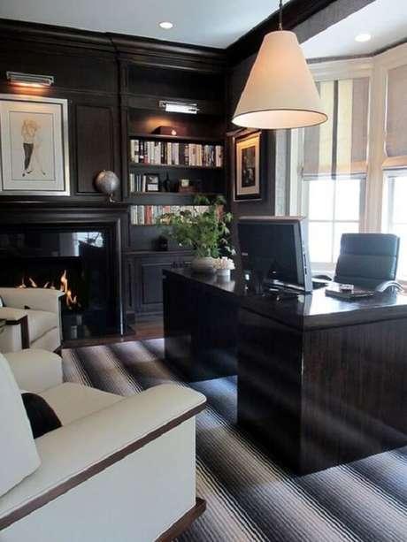21. Decoração sofisticada com escrivaninha preta e cadeira de couro. Fonte: Pinterest