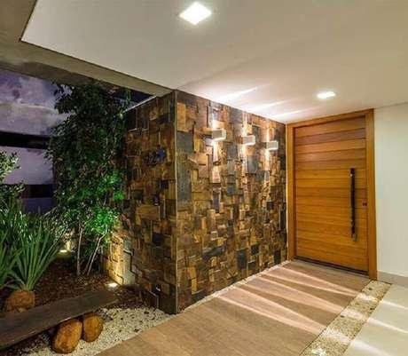 27. Entrada de casa com porta de madeira e revestimento pedra ferro em cubos – Foto: URBEM Arquitetura Ltda