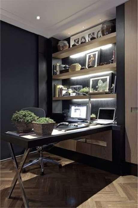 22. Escrivaninha preta em formato l. Sua estrutura está apoiada na estante de três andares com iluminação embutida. Fonte: Pinterest