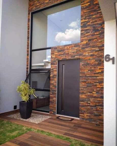 31. Fachada com pedra ferro e parede de vidro para mesclar estilos diferentes – Foto: Ana Paula Luz