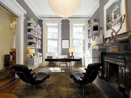 39. Home office com decoração elegante dispõe da presença de umamesa preta e poltronas na mesma tonalidade. Fonte: Pinterest