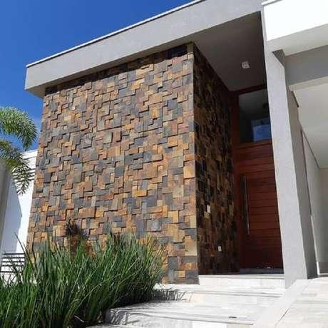 38. Pedra ferro fachada moderna com porta de madeira – Foto: Decor Salteado