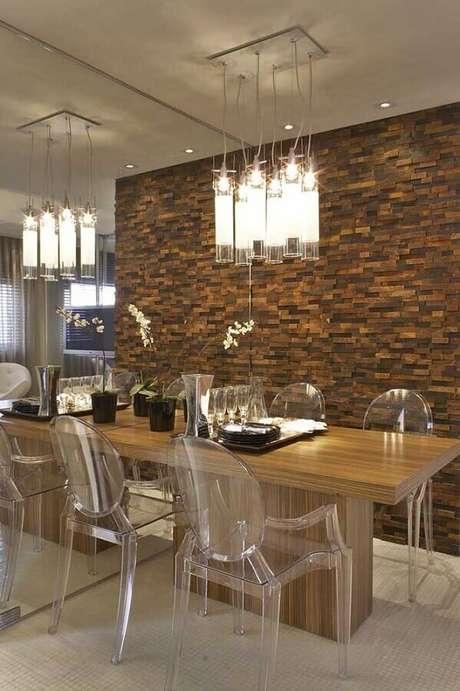 42. Pedra ferro para decoração de sala de jantar moderna com cadeiras de acrílico transparente e luminária transparente – Foto: Shopping das Pedras
