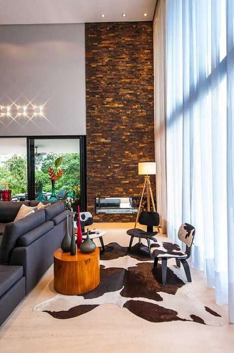 8. Decoração sofisticada para sala de estar com lareira e revestimento pedra ferro – Foto: Galeria da Arquitetura