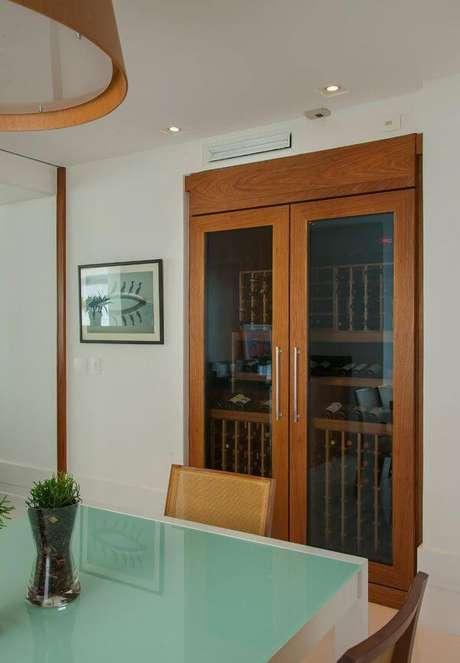 18. Adega de madeira com portas de vidro para sala de estar – Por: In House