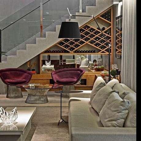 34. Com a escada logo ao lado da sala de estar, a adega de madeira ficou ainda mais bonita – Viva Decora