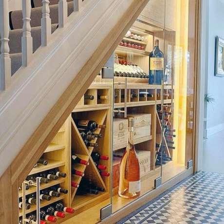 50. Adega de vinho de madeira embaixo da escada com porta de vidro – Por: Revista Viva Decor